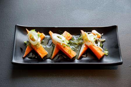 Enfoque suave de palito de cangrejo espolvoreado con hierba de limón en rodajas y cebolleta en rodajas en un plato negro, listo para comer o servir, enfoque selectivo, sobre fondo oscuro Foto de archivo
