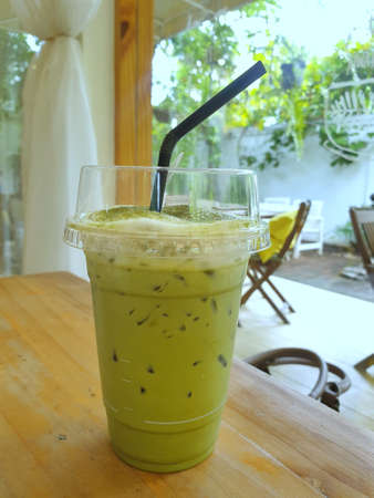 Selective focus of iced green tea on wooden table in café restaurant, Summer drink, ready to eat, relaxed time, Vertical