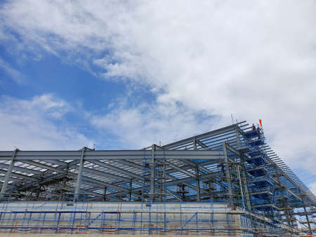 The structure of building with blue sky and clound as a background, Steel construction in large construction site, Space for text in template Stock fotó