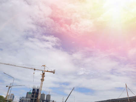 Looking up of tower crane on sky and cloud with sun shining as a background in the construction site, Space for text in template Stock fotó