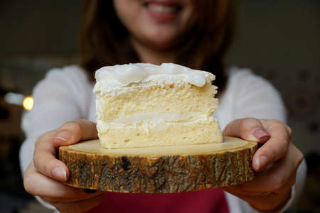 Selective focus of coconut cake on wooden table with blurred woman as a background in café restaurant, ready to eat