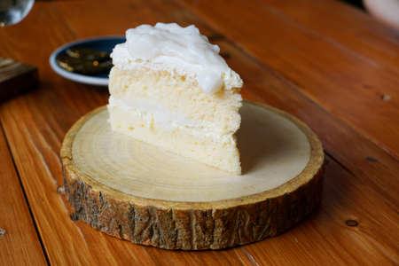 Selective focus of coconut cake on wooden cutting board in café restaurant, ready to eat or serve