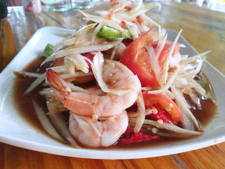 Thai food style, Selective focus of papaya salad with tomato, shrimp, chili and bean on wooden table, This food is most popular, Som Tum is Thai traditional Stock Photo