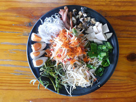 Thai food style, Top view of papaya salad set in black plate on wooden table, Space for text in template, healthy food concept, Som Tum tad is Thai traditional
