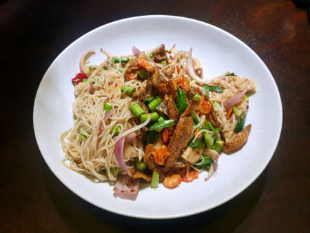 Papaya Salad with Vermicelli and Salted Crab in white plate on wooden table in restaurant, This food is most popular Thai food, Som Tum Kha Nom Jeen is thai traditional Stock Photo