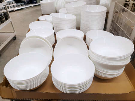 Top view of empty white plate and bowl on shelf for sale in supermarket