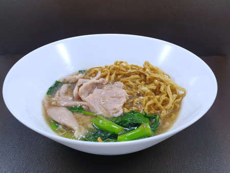 Top view of fried noodle with pork and chinese kale on wooden table as a background, This food is most popular and simple food (Rad Na), Ready to eat