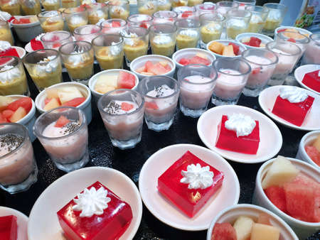 Top view of sweet red strawberry jelly topped with whip cream, chocolate mousse, strawberry yoghurts and mixed fruit in cup as a background in restaurant, summer dessert
