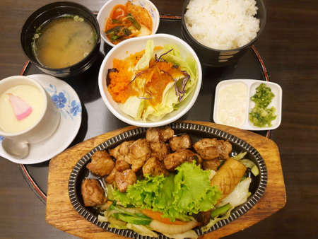 Japanese food style, Top view of buta steak with mixed vegetable salad, Kimchi, Steamed egg and rice on wooden table at restaurant, Space for text in template