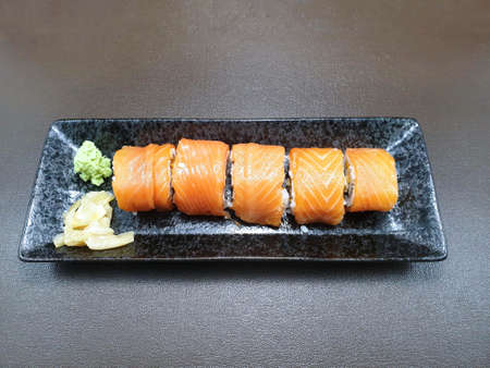 Japanese food style, Top view of salmon roll with wasabi and pickled ginger isolated on dark background, Ready to eat or serve
