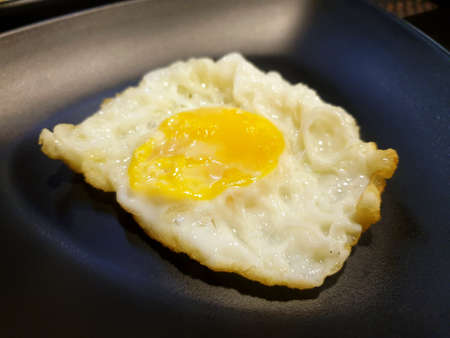 Top view of fried egg on dark background, Sunny side Up, Ready to eat or serve