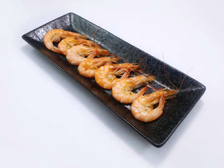 Top view of grilled prawns in black plate isolated on white background, Ready to eat or serve