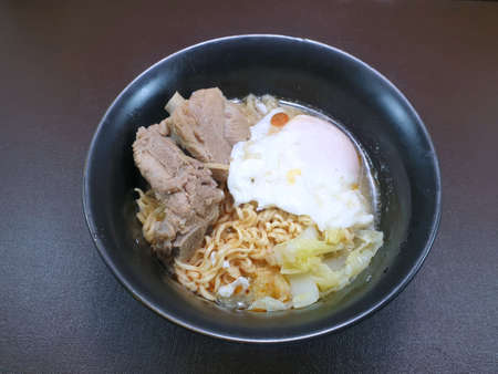 Top view of noodle with boiled egg and pork bones, hot and Sour Soup in white bowl, Space for text in template