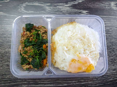 Thai food style, Rice topped with fried egg and stir fried minced pork with holy basil leaves in lunch box, This food is most popular Thai food (Pad kra pao)