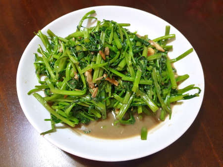 Top view of fried water spinach seasoned with chili and soy sauce on white plate on wooden table in restaurant Stock fotó