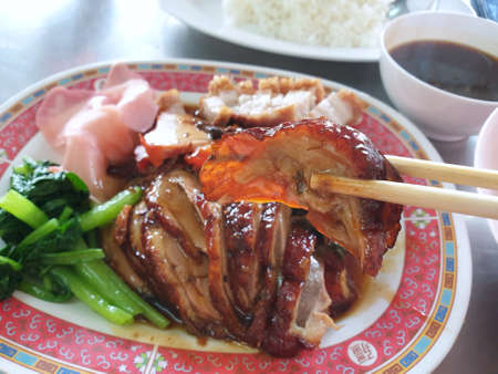 Chinese food style, Selective focus of chopsticks holding roasted duck in restaurant