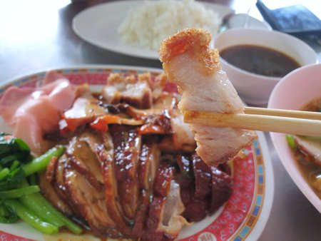 Selective focus of chopsticks holding fried pork crackling slice in restaurant