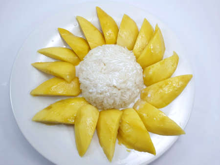 Top view of Thai mango sticky rice topped with coconut cream on white plate isolated on white background, This food is most popular Thai derrest, Kao neaw ma moung is Thai traditional Stock fotó