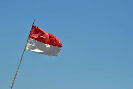 Indonesian flag fluttering below blue sky 스톡 콘텐츠