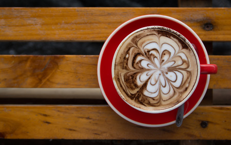 Red cup of hot coffee with milk foam draw as flower on brown wooden table in contrast style.