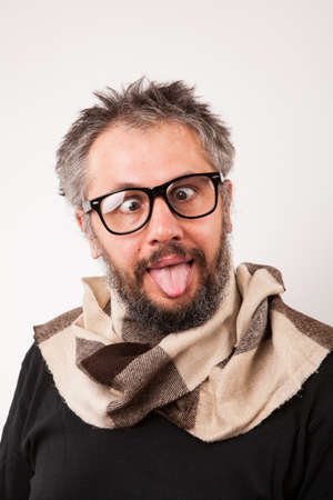 einstein: Crazy looking old man with grey beard with nerd big glasses show tongue rolling eyes Stock Photo