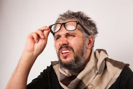caucasian man: Crazy looking thoughtful old man with grey beard looking from nerd big glasses
