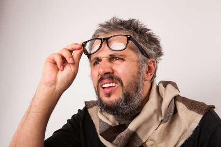 persona mayor: Loco buscando anciano reflexivo con barba gris que mira de grandes gafas nerd