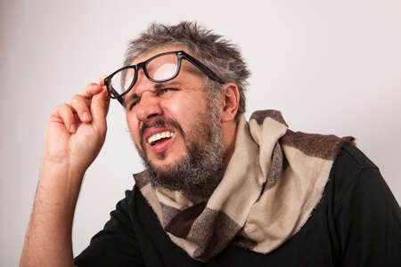 man mouth: Crazy looking thoughtful old blind man with grey beard looking from nerd big glasses Stock Photo