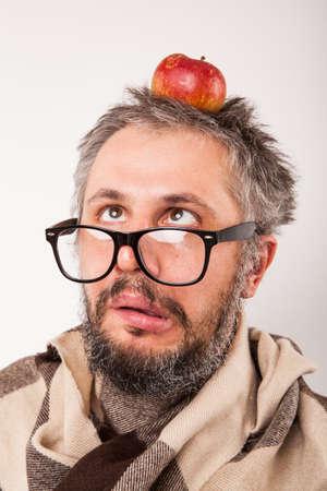grumpy: Old grumpy man with beard and big nerd glasses with apple on head Stock Photo