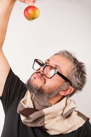 grumpy old man: Old grumpy man with beard and big nerd glasses looking up on the apple Stock Photo