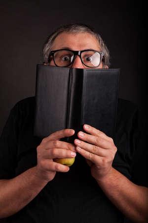 sleek: Old man with beard and big nerd glasses hides behind big sleek leather book Stock Photo