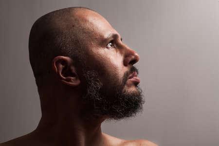 hombre desnudo: hombre calvo con barba de perfil en estudio de fondo oscuro mirando lados