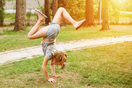 Little girl child doing exercises gymnastic outdoor in the park for fun at sunny day Stockfoto