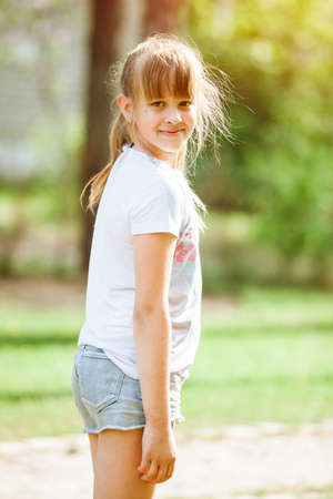 Portrait of little girl child outdoor in park on a sunny day. Teenage girl - Natural lifestyle image taken in May. Light brown long hair in ponytail. Blurred background.
