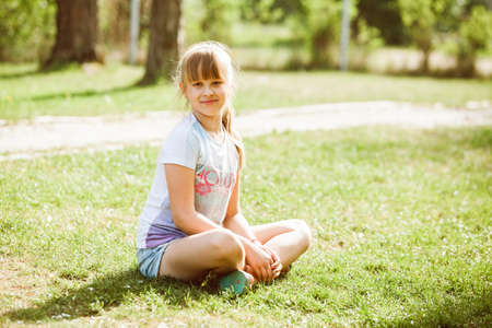 Portrait of little girl child outdoor in park sitting on grass at sunny day. Teenage girl - Natural lifestyle image taken in May. Light brown long hair in ponytail. Blurred background. 版權商用圖片