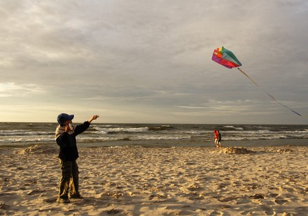 Boy on beach playing with a kite photo