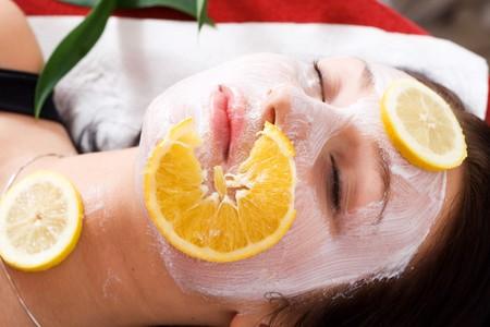 Kobieta w salonie kosmetycznym z owoców i maska na twarzy.