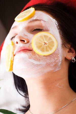 Kobieta w salonie kosmetycznym z maską i owoców na twarzy.