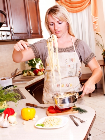 A woman cooking dinner in the kitchen. Healthy Eating photo