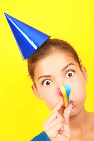 Funny party woman in blue on yellow background. Beautiful mixed race  asian caucasian model with party hat blowing a party blower at the camera.  photo