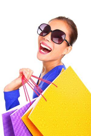 excitacion: Mujer riendo mientras compras. Chica excitada caminar mirando hacia atr�s con sus bolsas de compra sobre sus hombros. Aislado sobre fondo blanco. Foto de archivo