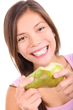 Beautiful young woman eating a pear very excited. Isolated on white background. photo