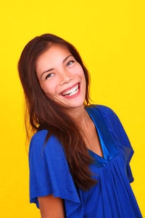 Young mixed race person laughing on yellow background.