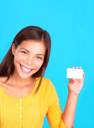 Beautiful young ethnic woman presenting a blank business card, on a bright blue background. photo