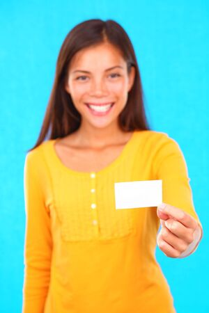 Exotic young woman on colorful background holding a blank business card with copy space.  photo