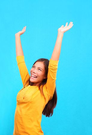woman arms up: Successful woman raising her hands up in the air in hapiness on a colorful background. Stock Photo