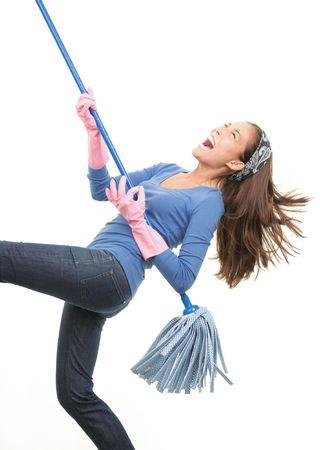 ama de casa: Mujer de limpieza que se divierten por tocar la guitarra de aire con el mop. Aislado sobre fondo blanco.