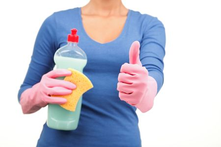 Happy house cleaning concept. Woman holding liquid soap and sponge giving a thumbs up to the camera. Shallow depth of field, focus on thumb. photo