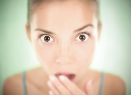 gasping: Closeup of a shocked woman  surprise expression. Shallow depth of field on a green background.