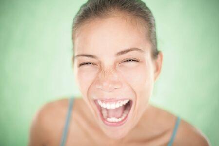 excitacion: Muy expresiva asi�tica joven riendo o gritando de alegr�a. Poco profunda de la profundidad de campo sobre fondo verde. Foto de archivo